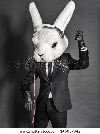 Dj man inside white rabbit head mask and headphones   - stock photo