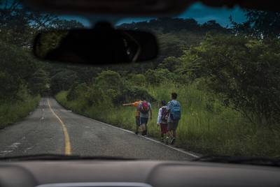 Migrants walk through Highway México 307 on Oct. 21 near Palenque, Chiapas. The highway is also known by the locals as 'El gran corredor del pacífico del migrante,