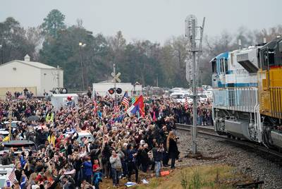 People pay their respects as the train carrying the casket of former President George H.W. Bush passes by along the route from Spring to College Station on Thursday, Dec. 6, 2018.