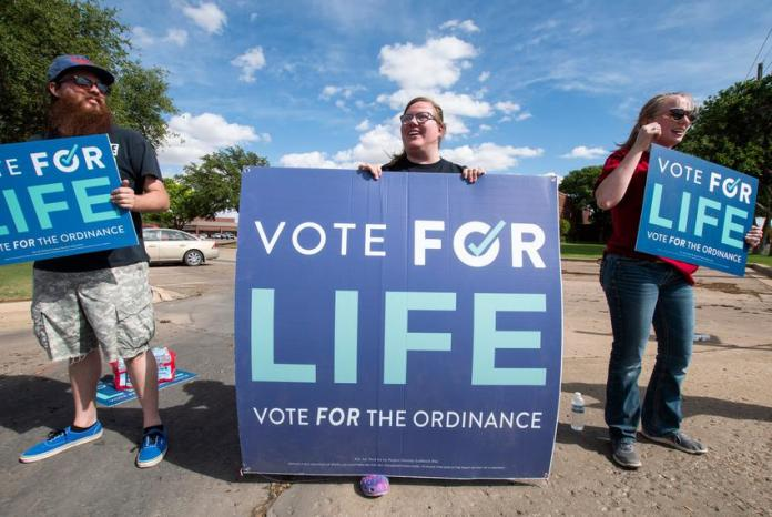 Josh Upchurch, Shelby Martin and Hailee Roberts campaign for Proposition A at the corner of Quaker Ave. and 82nd Street on S…