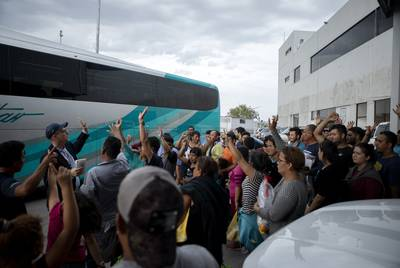 A group of migrants raise their hands after Texas Tribune reporter Jay Root asked how many planned on returning to Central America. The group requested asylum in the United States, but were promptly returned to Mexico to await their court dates. July 22, 2019.