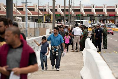 A group of migrants walk across Internation Bridge Two into Mexico from the United States. The group requested asylum in the United States, but were returned to Mexico to await their court proceedings. July 23, 2019.