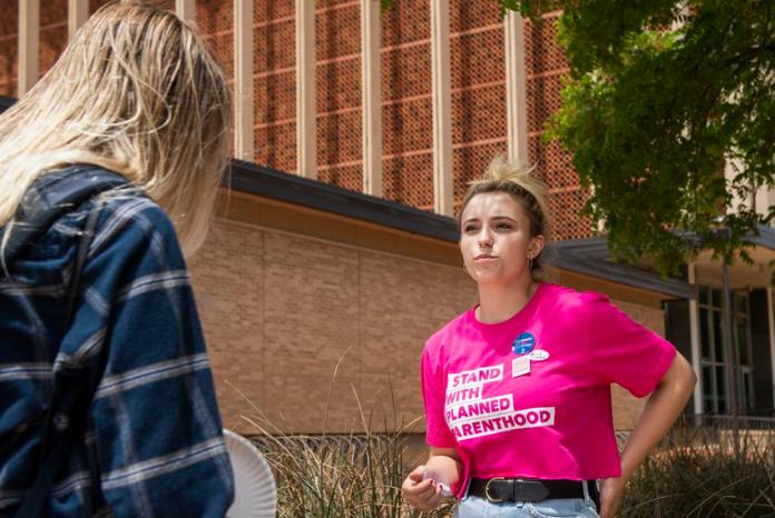 Sofia Bell talks with a potential voter about voting against Proposition A on the Texas Tech University campus on May 1, 202…