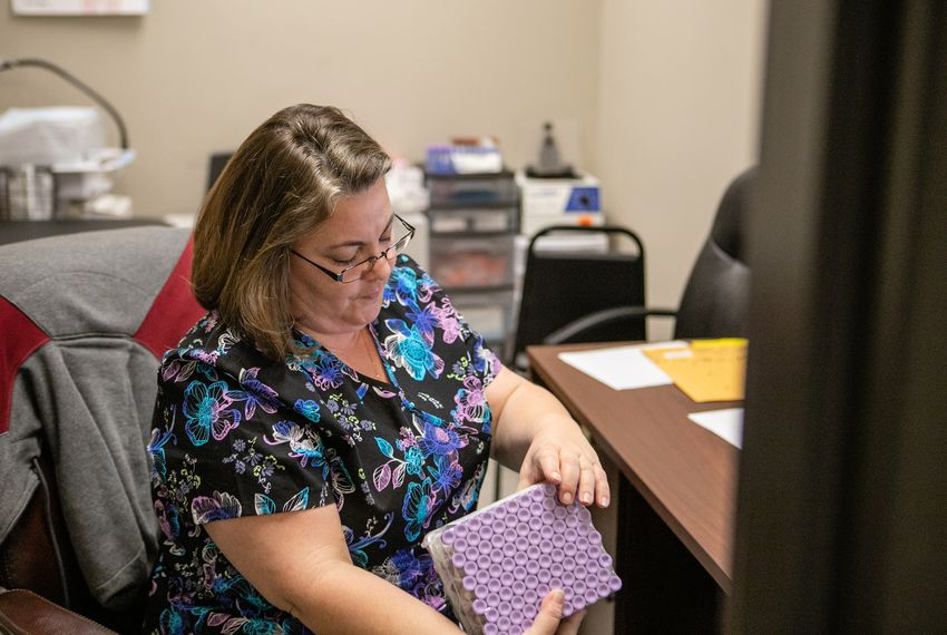 Kristal Macaluso, a phlebotomist at Western Hills Clinic, reorganizes medical supplies at the clinic, part of MHMR of Tarrant County.