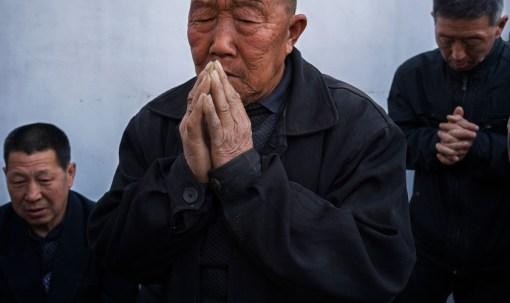 Chineses orando em uma igreja subterrânea no quintal de uma casa. (Foto: Adam Dean/Panos)