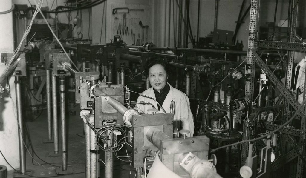 Chien-Shiung Wu is pictured in a labratory setting. She is wearing a white lab coat