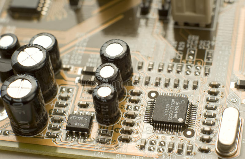Capacitors And Microchips On Circuit Board Stock Photo