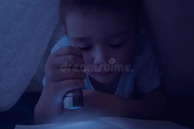 Enfant De Yound Lisant Le Livre Interessant La Nuit A L Aide