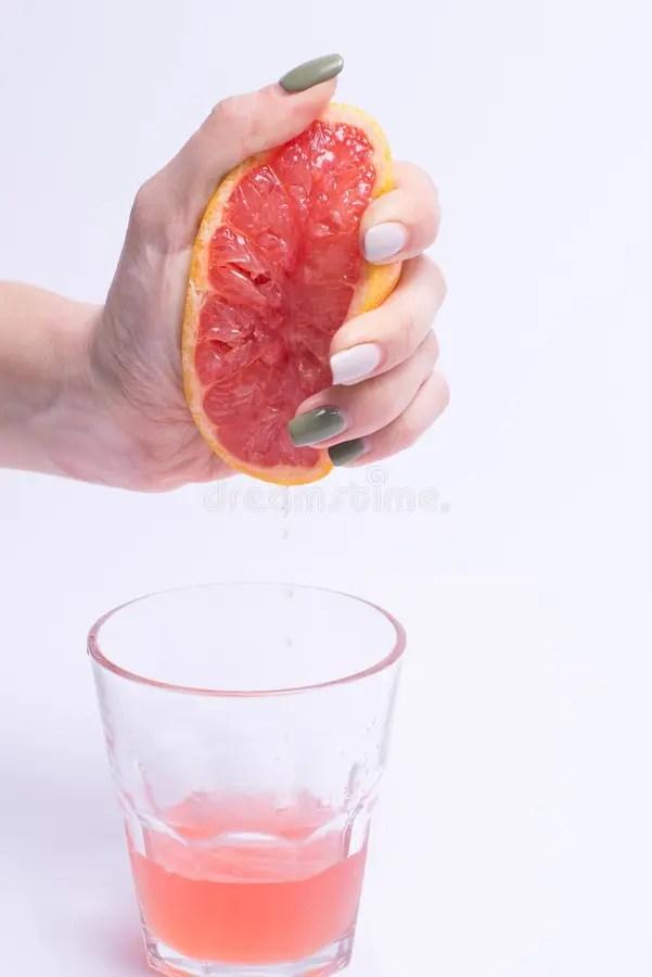 Female Hand Squeezes Of A Grapefruit Grapefruit Juice On ...