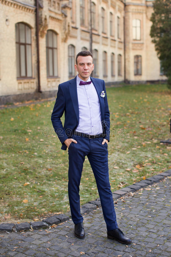 The Groom In A Blue Suit And Bow Tie Posing In The Photo