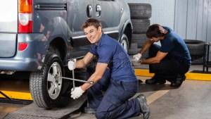 Happy Mechanic Fixing Car Tire At Repair Shop Stock Photo Image 61544321