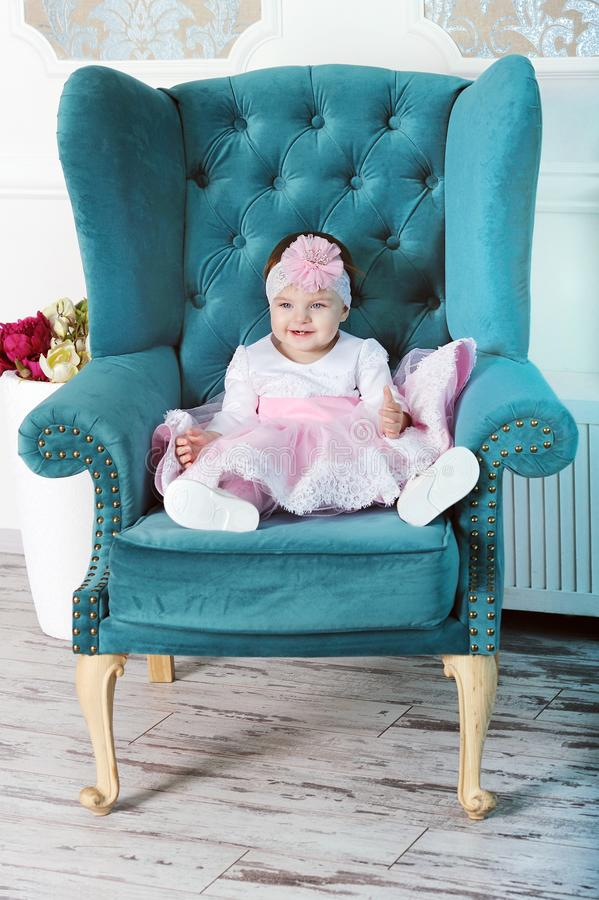 Happy Young Infant Girl Sitting In Big Chair Stock Photo