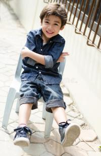 Little Boy Sitting On Chair Portrait With Smiling Outdoor