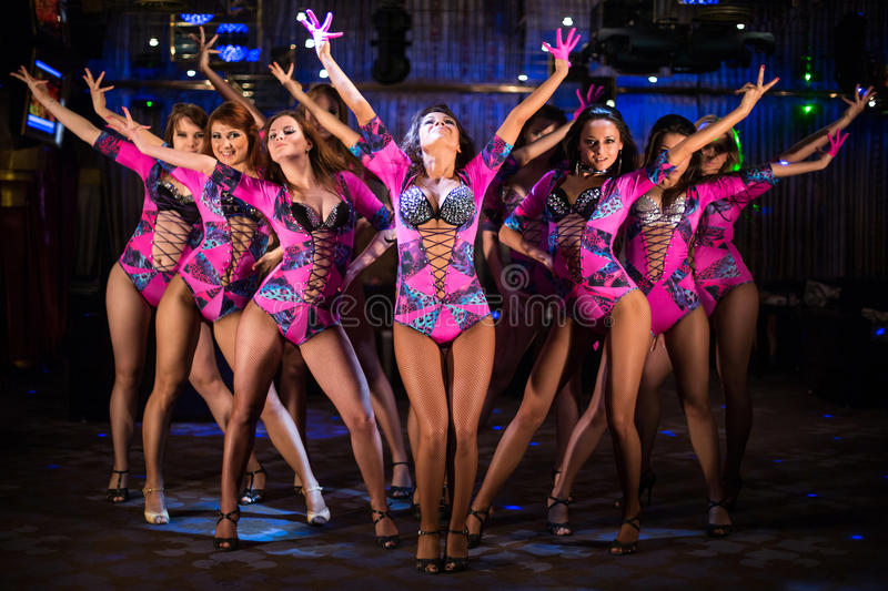 Nine Showgirls In Purple Costumes With Raised Hands