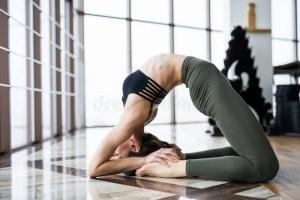 yoga background practice studio concept sirsasana bandha setu near window woman