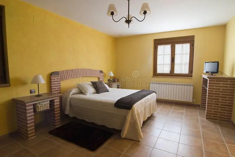 Slaapkamer In Geel En Bakstenen Stock Afbeelding