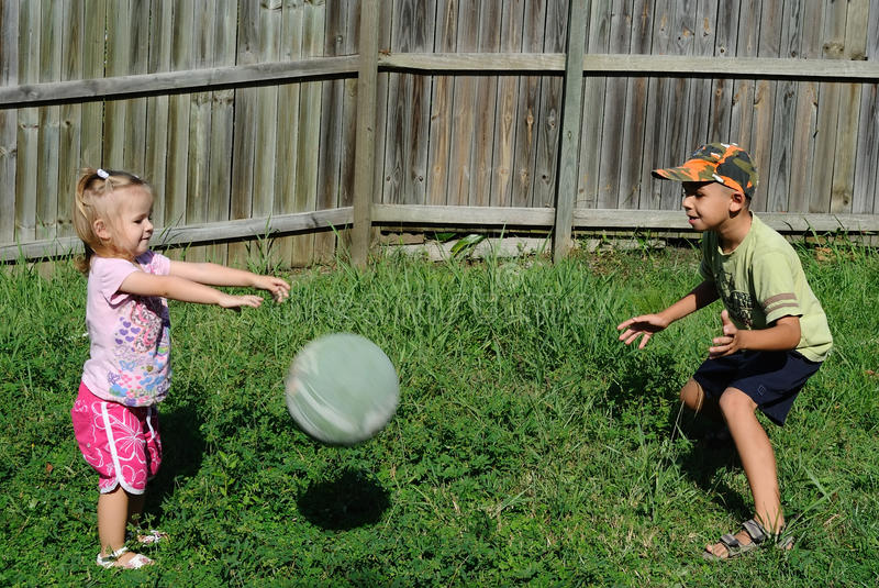 two kids playing ball in a backyard royalty