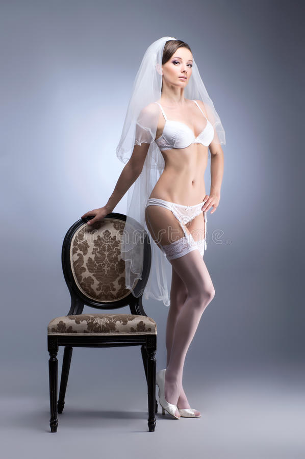 A Young Brunette Bride In White Erotic Lingerie Stock