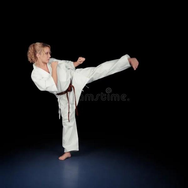 Young Karate Woman In White Kimono Kicking Stock