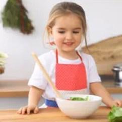 Kitchen Kid Yellow Towels 审查她的玩具熊的小女孩由听诊器医疗保健 儿童患者信任概念库存图片 少许烹调女孩厨房孩子切的和混合的蕃茄和绿叶健康膳食的