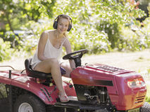 young woman driving ride mower