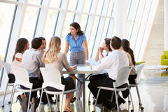 Ten people sitting at a business meeting, listening to a woman train them.