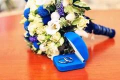 Hochzeitsringe Mit Blume Auf Blauem Hintergrund Stockfotos
