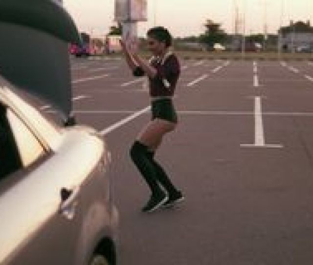 Young Woman In The Crop Top And Shorts Dance Twerk By The Car On The Parking