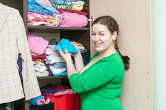 Young woman organizing clothes in the wardrobe Stock Photography