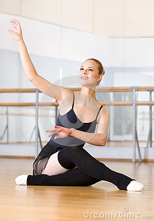 ballet dancer does exercises sitting wooden floor works out classroom barre mirrors 33918802