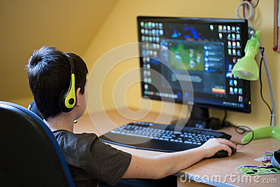 Boy Using Computer At Home Playing Game Stock Photo