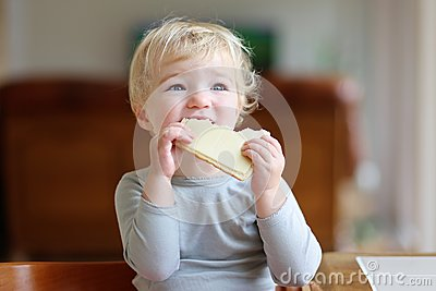 Funny Little Girl Eating Sandwich At Home Stock Photo