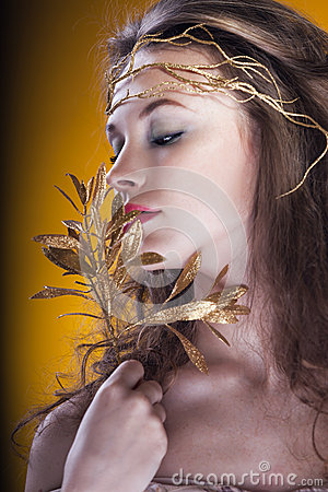 girl with a gold branch in hair on yellow background royalty free stock image image