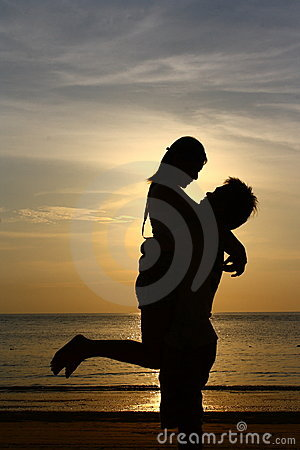 Happy Couple On Sunset Beach  Silhouette Royalty Free
