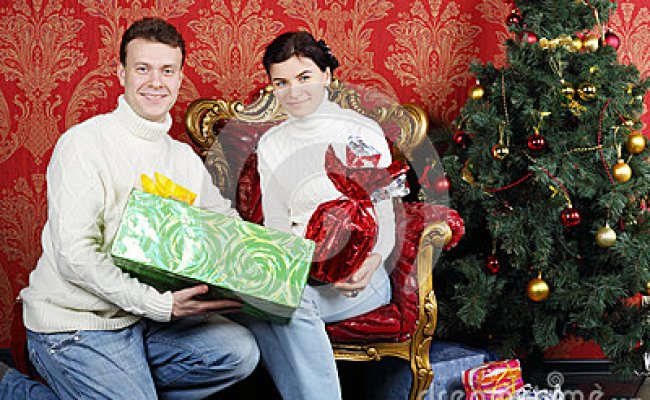 Husband And Wife With Gifts Smile Near Christmas Tree