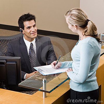 Receptionist Greeting Woman At Front Desk Royalty Free