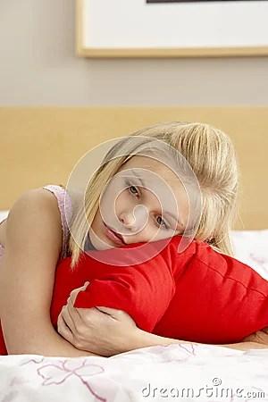 Sad Teenage Girl In Bedroom Hugging Pillow Royalty Free