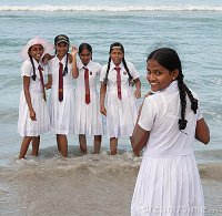 Schoolgirls In Uniform Playing On The Beach Editorial
