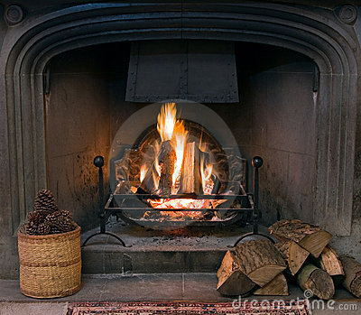 Stone Fireplace With A Lit Roaring Fire Royalty Free Stock