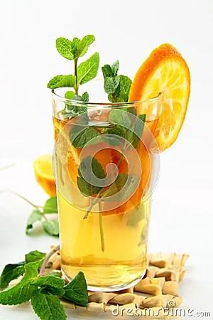 Thee met sinaasappel en takken van munt