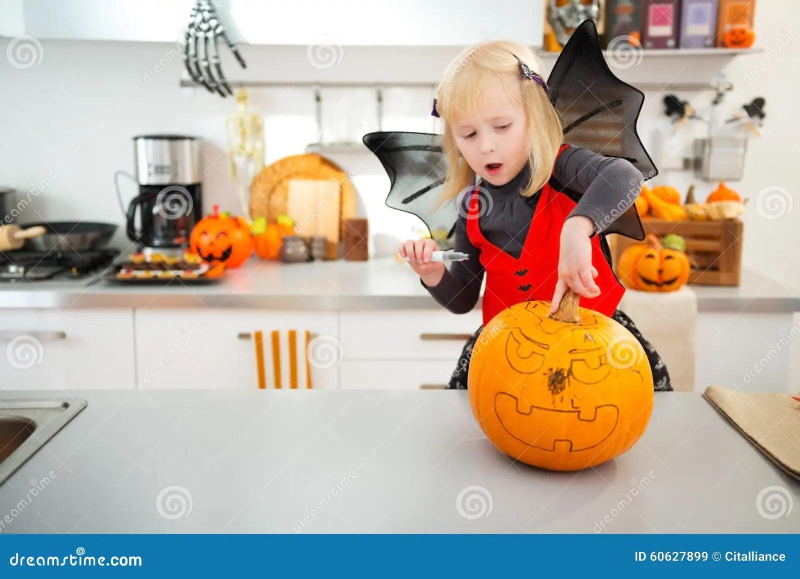 kitchen lanterns chandeliers 万圣夜打扮了创造南瓜杰克o灯笼的女孩库存图片 图片包括有服装 准备 棒服装的感兴趣的白肤金发的女孩使用雕刻的钢板蜡纸在万圣夜党的大橙色南瓜杰克o灯笼在装饰的厨房里传统秋天假日