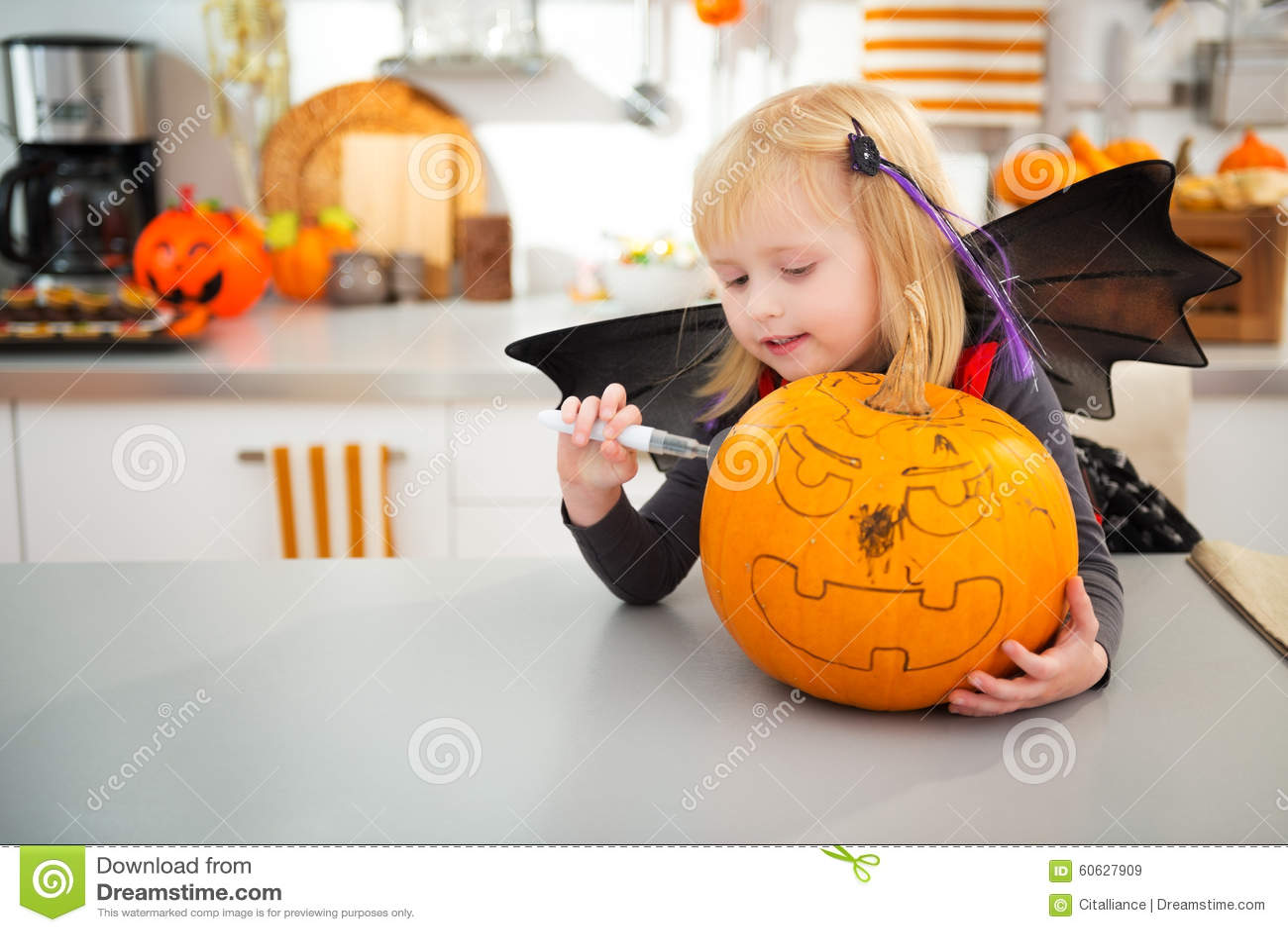 kitchen lanterns island design 万圣夜打扮了创造大南瓜杰克o灯笼的女孩库存图片 图片包括有现代 厨房 微笑的万圣夜打扮了创造大橙色南瓜杰克o灯笼的女孩在装饰的厨房传统秋天假日