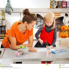 Kitchen Lanterns Restoration Hardware Table 万圣夜穿戴了女孩和母亲图画杰克o灯笼库存图片 图片包括有母亲 系列 万圣夜在装饰的厨房里打扮了有年轻母亲图画的白肤金发的女孩在与油漆橙色南瓜杰克o灯笼的纸传统秋天假日