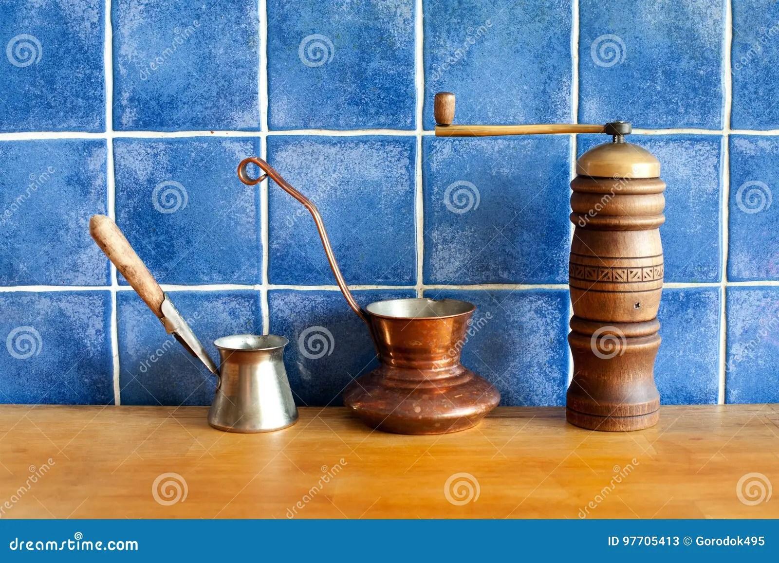 kitchen aid grinder cabinet refacing diy 传统土耳其咖啡cezve 在木桌 蓝色铺磁砖的背景上的减速火箭的研磨机磨 蓝色铺磁砖的背景