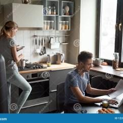 Mobile Home Kitchens How To Remodel Your Kitchen 使用膝上型计算机和智能手机的年轻夫妇在厨房里库存照片 图片包括有系列 使用膝上型计算机的年轻夫妇和智能手机在厨房里 在家在网上工作微笑的人 当他的烹调与电话apps 家庭早晨生活方式与小配件或设备瘾概念时的妻子