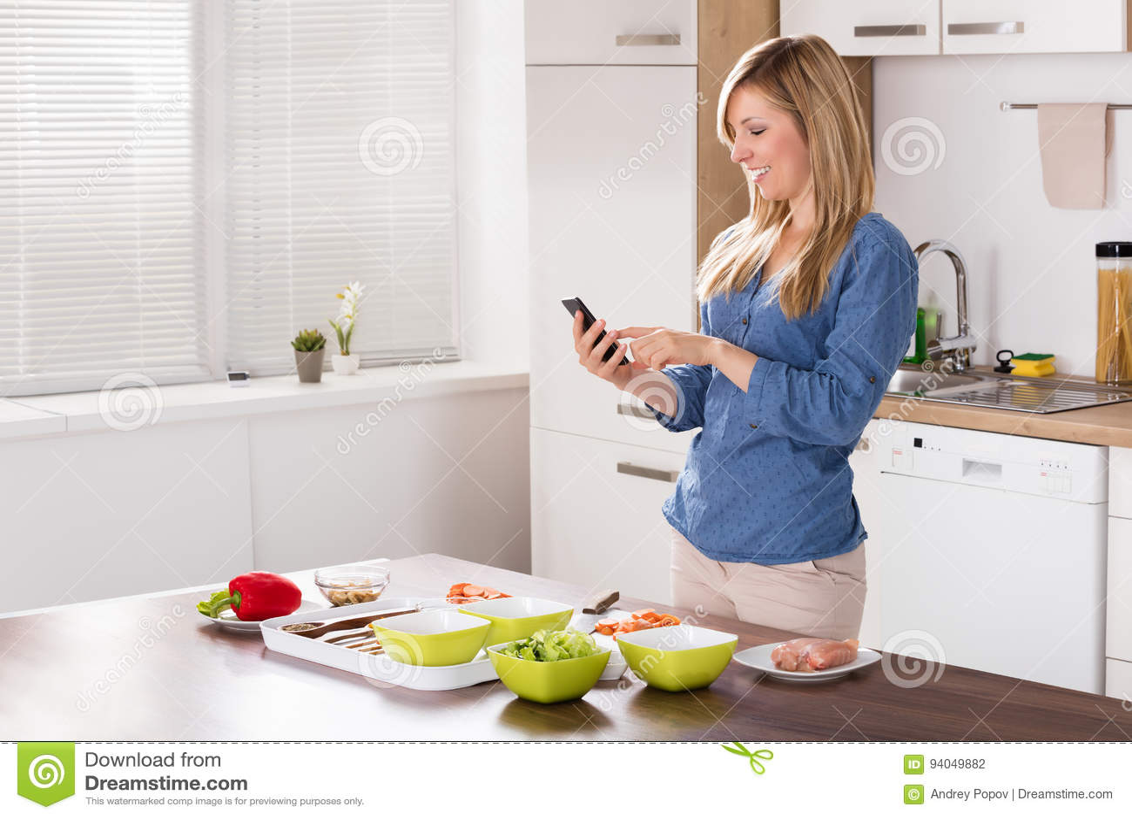 kitchen phone copper pendant light 使用移动电话的微笑的妇女在厨房库存照片 图片包括有营养 烹调 设备 使用移动电话的微笑的妇女在厨房