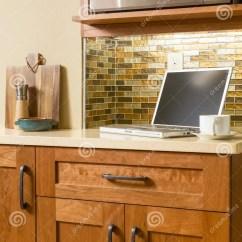 Portable Kitchen Commercial Tables 便携式计算机和咖啡杯在柜台在当代家庭厨房里有木内阁和玻璃瓦片 便携式计算机和咖啡杯在柜台在当代家庭厨房里有木内阁和