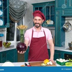 Kitchen Prep Table Italian Cabinets 厨师拿着红叶卷心菜手中在厨房厨师新鲜蔬菜为烹调在桌上做准备围裙的愉快 厨师拿着红叶卷心菜手中在厨房厨师新鲜蔬菜为烹调在桌上做准备围裙的愉快的人在烹调前显示大红叶卷心菜圆白菜和辣椒粉是菜为吃