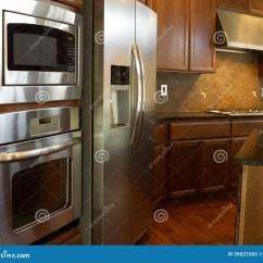 In Stock Kitchens Reglaze Kitchen Sink 厨房器具库存图片 图片包括有计数器 Backarrow 厨房 飞溅 现代 没 不锈钢装置的特写镜头照片在有石桌面和樱桃木内阁的现代住宅厨房里有硬木地板的