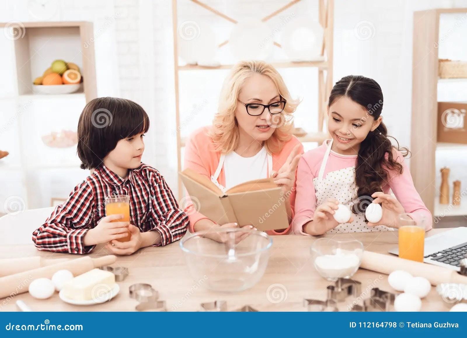kitchen apron for kids non slip rugs 围裙的美丽的祖母 与她的孙一起 看菜谱在厨房里库存照片 图片包括有 围裙的成人祖母 看菜谱在厨房里烘烤曲奇饼有她的孙的美丽的祖母在厨房里烘烤曲奇饼